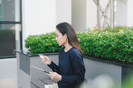 A pretty young asian business woman on bench outside office building