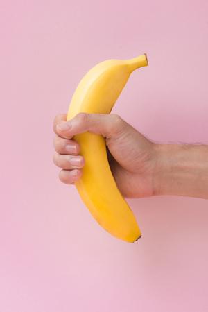 hand met banaan geïsoleerd op roze achtergrond. Stockfoto