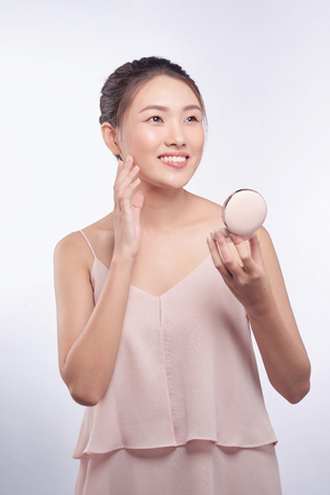 Young asian girl doing makeup, applying blusher to her cheek Stock Photo