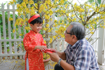 Grandfather giving lucky money to grandson on the first day of Vietnamese lunar new year Tet