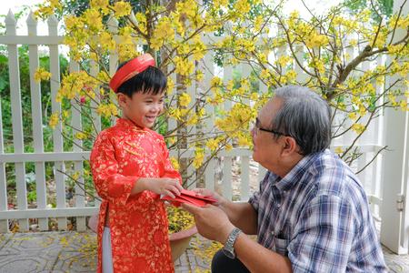 Großvater, der dem Enkel am ersten Tag des vietnamesischen Mondneujahrs Tet . Glücksgeld gibt