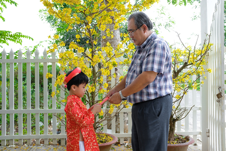 Grandfather giving lucky money to grandson on the first day of Vietnamese lunar new year Tet Standard-Bild - 116099553