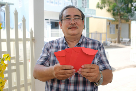 Asian man holding red envelope, lunar new year