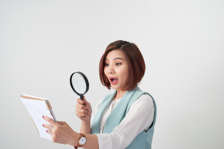 Woman carefully reading business contract with magnifying glass Stock Photo