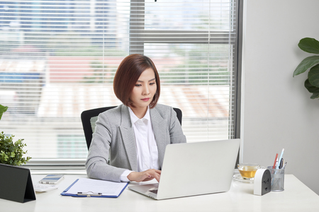 Beautiful young businesswoman in office Фото со стока