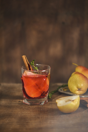 homemade hot mulled pear cider with a cinnamon stick on a wooden background