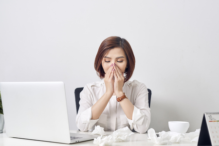 Sad exhausted woman with tissue suffering from cold while working with laptop at table Фото со стока - 116701380