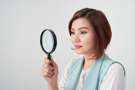 Close-up portrait of cheerful  woman in blue suite looking at camera through magnifying glass, isolated over white background Stock Photo