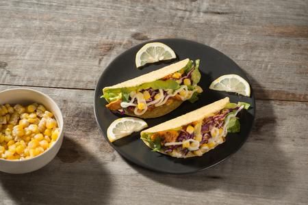 Traditioneller mexikanischer Taco mit Hühnchen und Gemüse auf Holztisch. Lateinamerikanisches Essen.