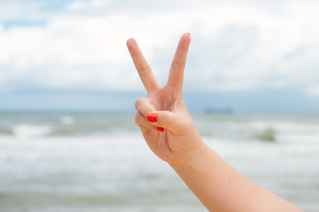 V sign victory concept at the sea.Feeling fresh.The atmosphere is refreshing and relaxing.