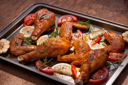 Baked chicken drumstick and wings on baking tray over dark wooden background. Stok Fotoğraf