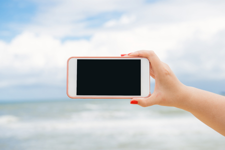 Mano della donna che mostra uno schermo orizzontale dello smartphone vuoto sulla spiaggia con il mare sullo sfondo