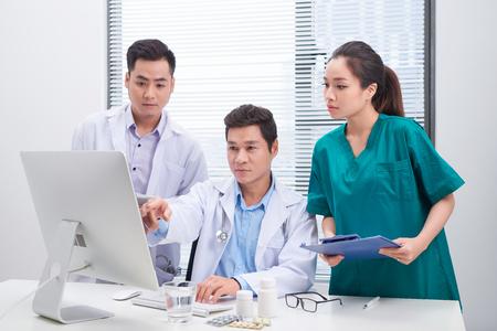 Tre medici che discutono i file dei pazienti in ufficio.