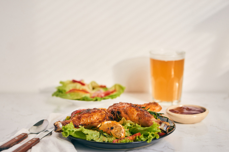Grilled chicken legs roasted on the grill on dark plate with tomato sauce in a bowl and lettuce leaves, glass mug of beer Stock Photo