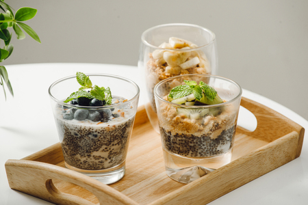 Fruits yogurt parfait with granola and chia seeds for healthy breakfast on wooden table Stock fotó