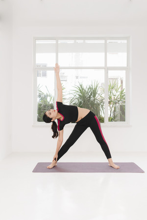 Young attractive woman practicing yoga, standing in Warrior two exercise, wearing sportswear, indoor full length near window Stock Photo