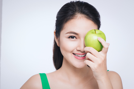 Attractive smiling young asian woman eating green apple isolated over white background.