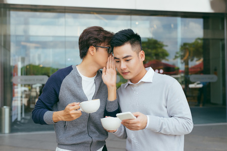 Businessman telling secret to his colleague in the office - Image