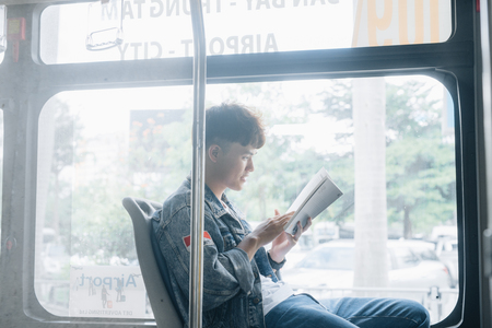 HO CHI MINH CITY, VIETNAM - 22 JULY, 2017: Transport: Transport. People in the bus. He reading book in transport.