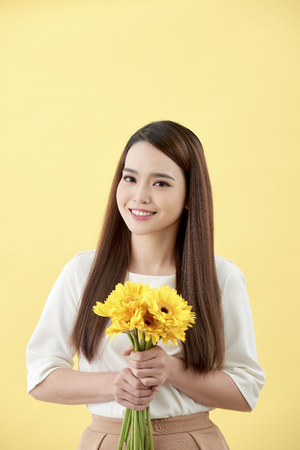 Asian lady holding a bunch of flower standing against a wall