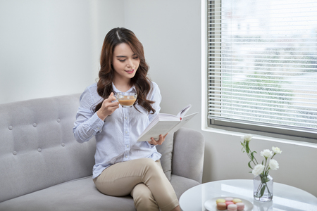 Young attractive woman read book and drink coffee sitting near window at home