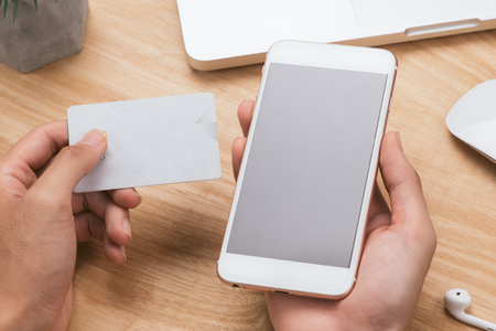 Hände, die Kreditkarte, Smartphone halten und Laptop verwenden. Online-Shopping-Konzept - Vintage-Ton und Flare gefiltert