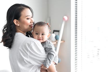 Belle jeune maman joue avec son bébé mignon et sourit en se tenant près de la fenêtre à la maison