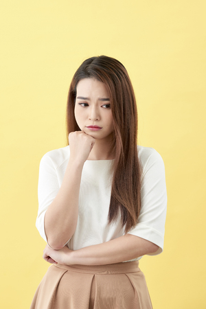 young pretty woman Concentrating hard on an idea, with a serious look and facing downwards, thinking with fist clenched pressing on chin. Stock Photo