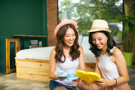 smiling beauty sisters preparing luggage in living room and looking at schedule list checking all baggage already prepared.