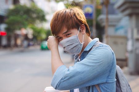 Hombre asiático en la calle con máscaras protectoras., Hombre enfermo con máscara con gripe y soplar la nariz en la servilleta como concepto de epidemia de gripe en la calle.