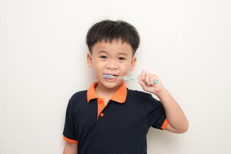 Little boy brushing his teeth on white background Stock Photo