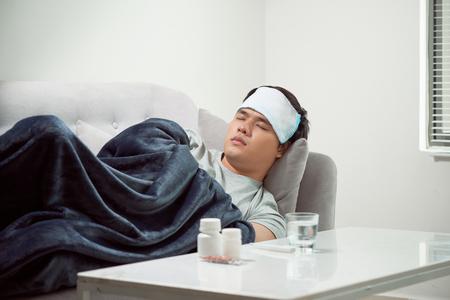 Malade homme gâché couché dans le canapé souffrant du virus de la grippe froide et hivernale ayant des comprimés de médecine dans le concept de soins de santé à la température sur le thermomètre Banque d'images