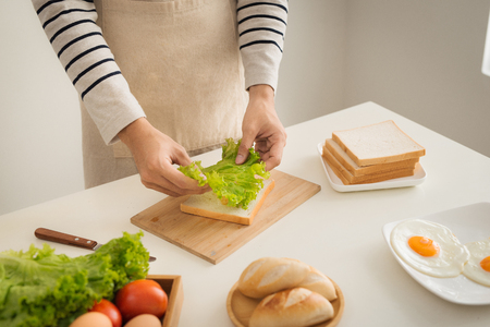 Preparing and eating breakfast at home in morning. 版權商用圖片
