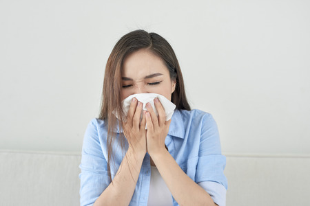 Picture of a sick young lady sitting on the couch and blowing her runny nose Stock Photo