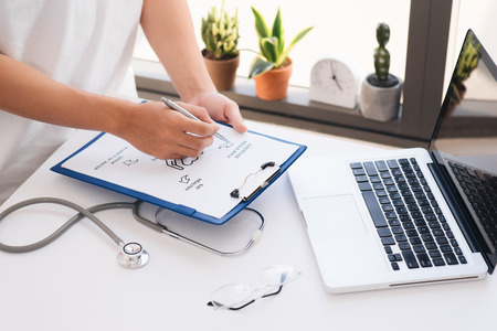Close up on hands. Asian female doctor with laptop and writing something on clipboard, prescription, paperwork,patient checklist paper or application form at a hospital. Stock Photo