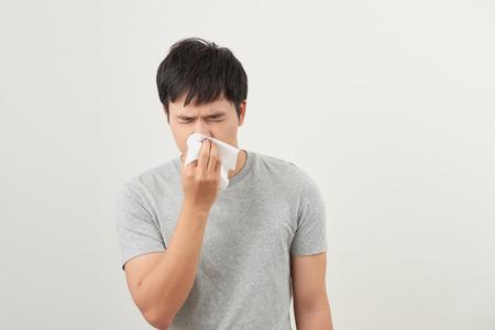 El hombre está enfermo y estornudando con fondo blanco, asiático