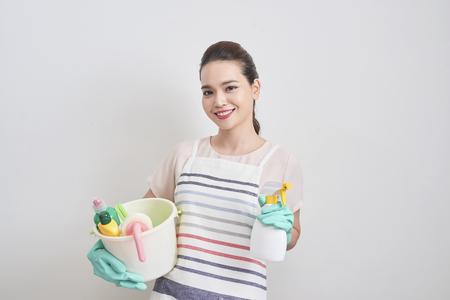 Retrato de mujer feliz sosteniendo en sus manos productos de limpieza mientras está de pie en casa y comienza a limpiar. Foto de archivo
