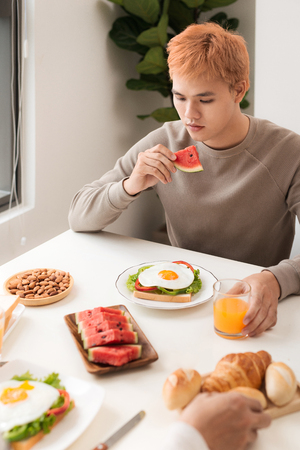 Men having breakfast with toasts at table