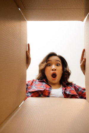 Smiling young woman opening a carton box, relocation and unpacking concept Stockfoto