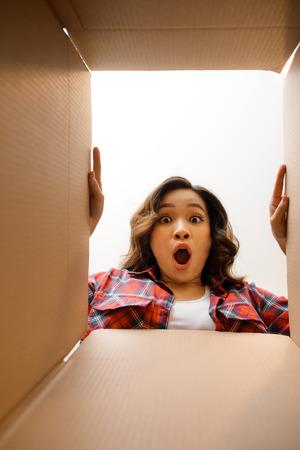 Sorridente giovane donna che apre una scatola di cartone, trasferimento e disimballaggio concept