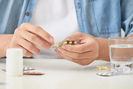 man taking pill out from blister pack at home