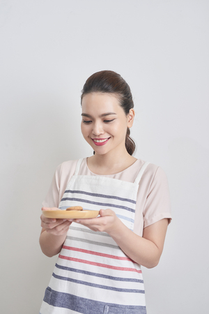 Young asian woman holding plate with homemade chocolate cookies Stock Photo
