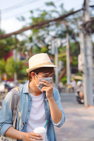 Young man in protective mask feeling bad on the street in the city with air pollution Stock Photo