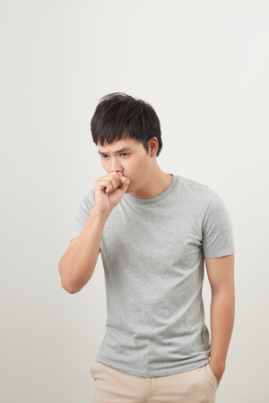 handsome man coughing into his fist, isolated on a white background
