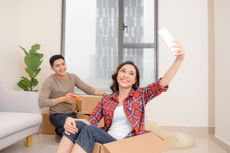 Happy attractive young couple is moving, making a selfie, cuddling and smiling while sitting among cardboard boxes