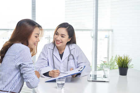 Female doctor talks to female patient in hospital office while writing on the patients health record on the table. Healthcare and medical service. Stock Photo