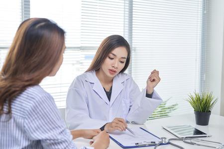 Ärztin spricht mit Patientin im Krankenhausbüro, während sie auf die Patientenakte auf dem Tisch schreibt. Gesundheitswesen und medizinischer Dienst. Standard-Bild