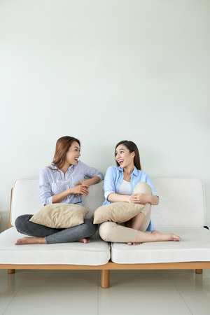 Two young beautiful cheerful girlfriends sitting on sofa at home laughing.