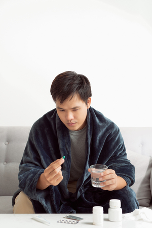 Handsome young man with pill and glass of water at home Stock Photo