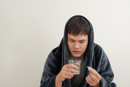 A young man is sick with flu, lies at home under a blanket, takes a pill Banco de Imagens